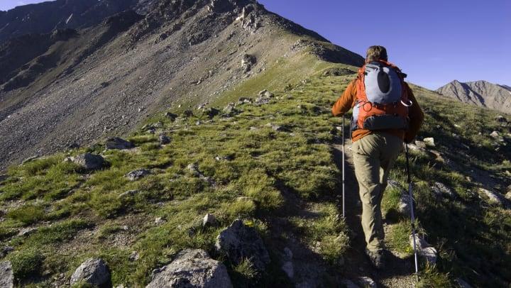 Man backpacks on a mountainous trail