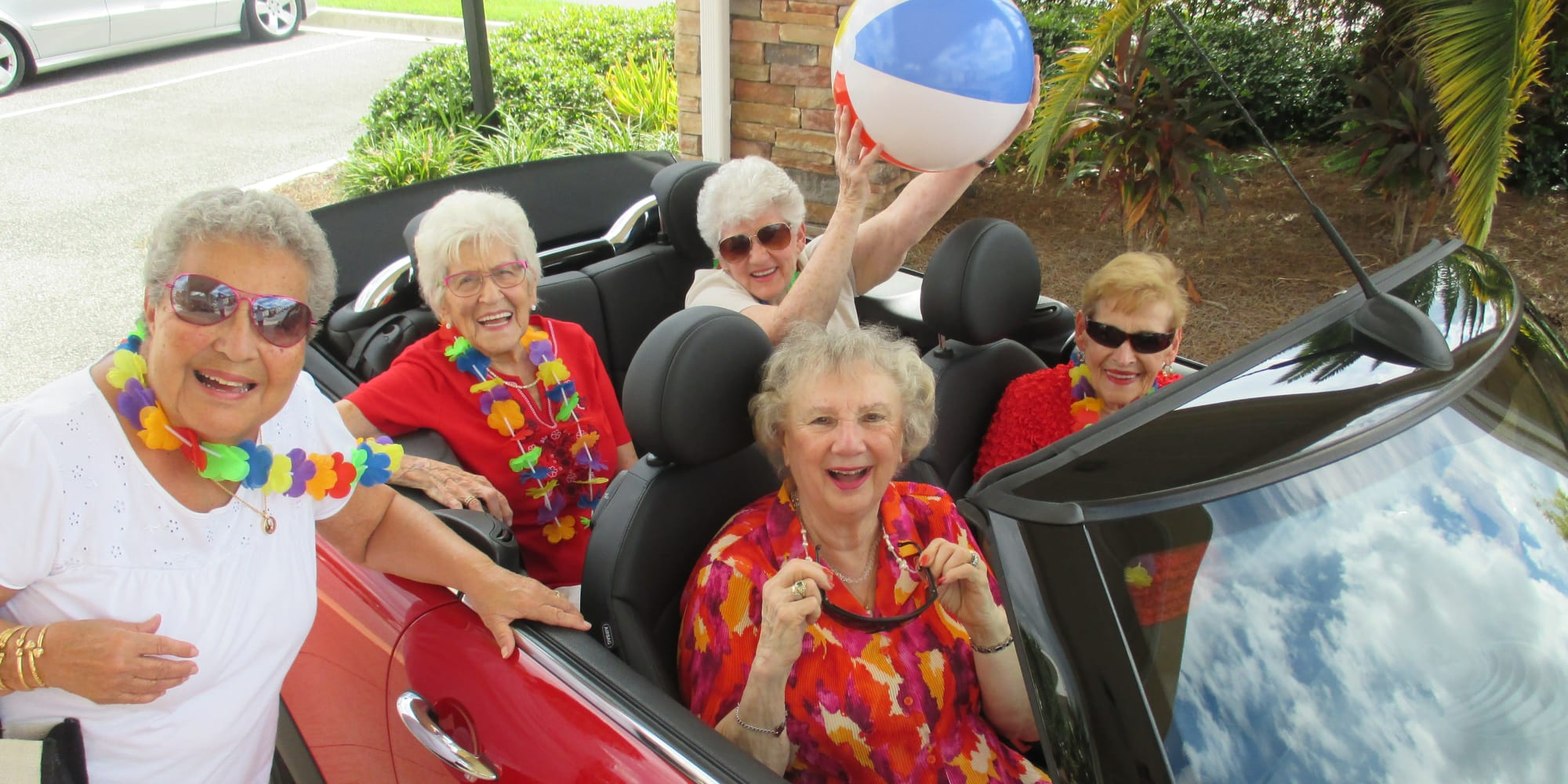 Happy residents in a convertible car at The Palms at La Quinta Assisted Living and Memory Care in La Quinta, California