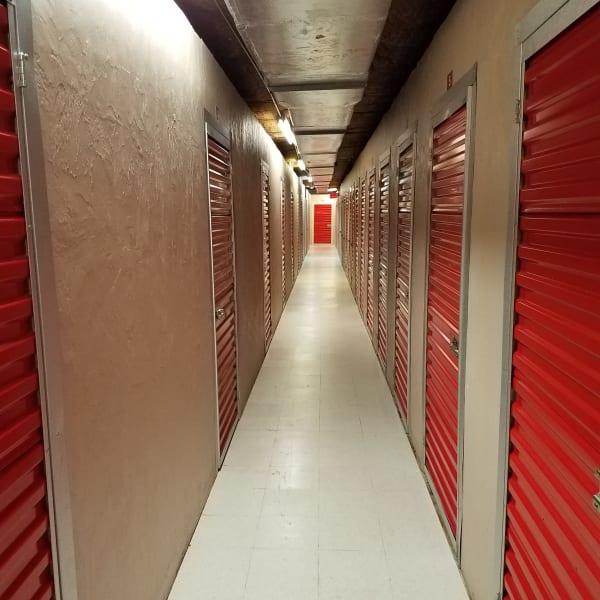 Indoor storage units with red doors at StorQuest Self Storage in Tampa, Florida