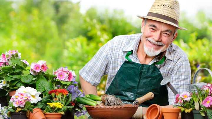 Elderly man smiling with flower pots infront of him on a table