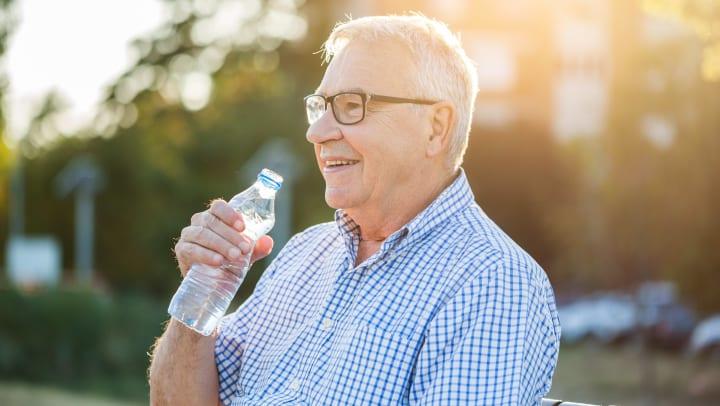 Senior drinking water outdoors