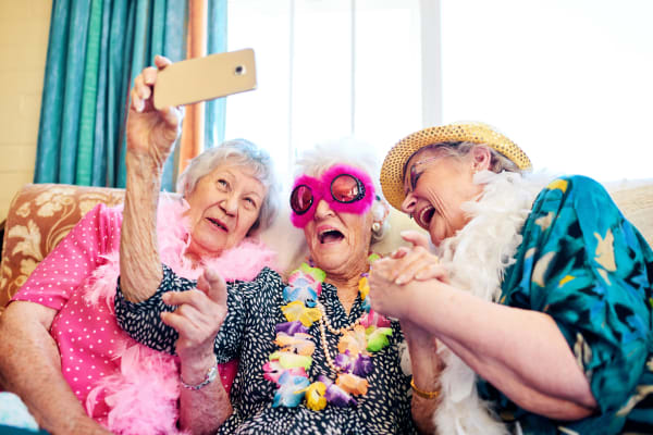 Three residents taking a photo together at Weatherly Court in Medford, Oregon