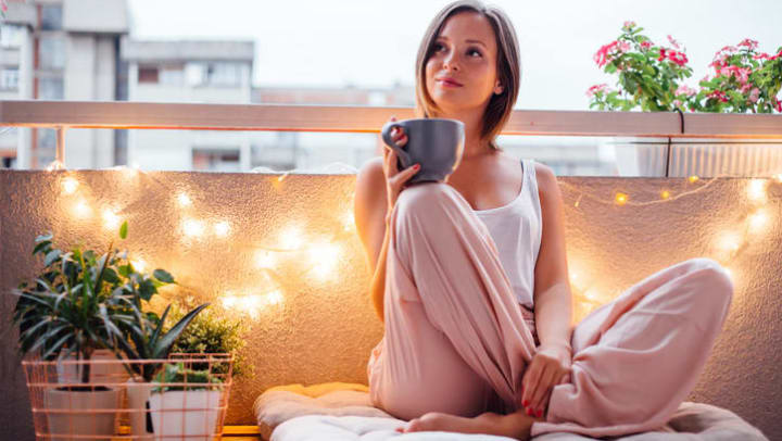 Girl holding a mug sitting on her balcony at {{location_name}}.