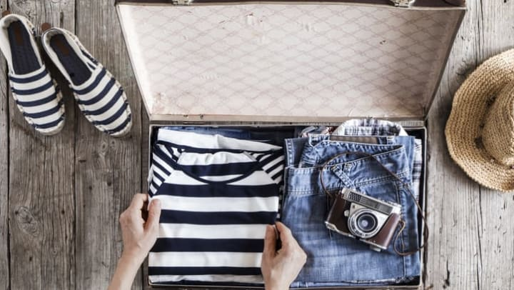 Picture of a person packing a suitcase with a shirt, jeans, and camera with shoes and straw hat on either side of the open suitcase near {{location_name}} in {{location_city}}, {{location_state_name}}