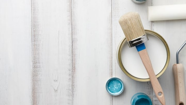 Top view of paint brush, sponge roller, paints, waxes and other painting or decorating supplies on white wooden plank.