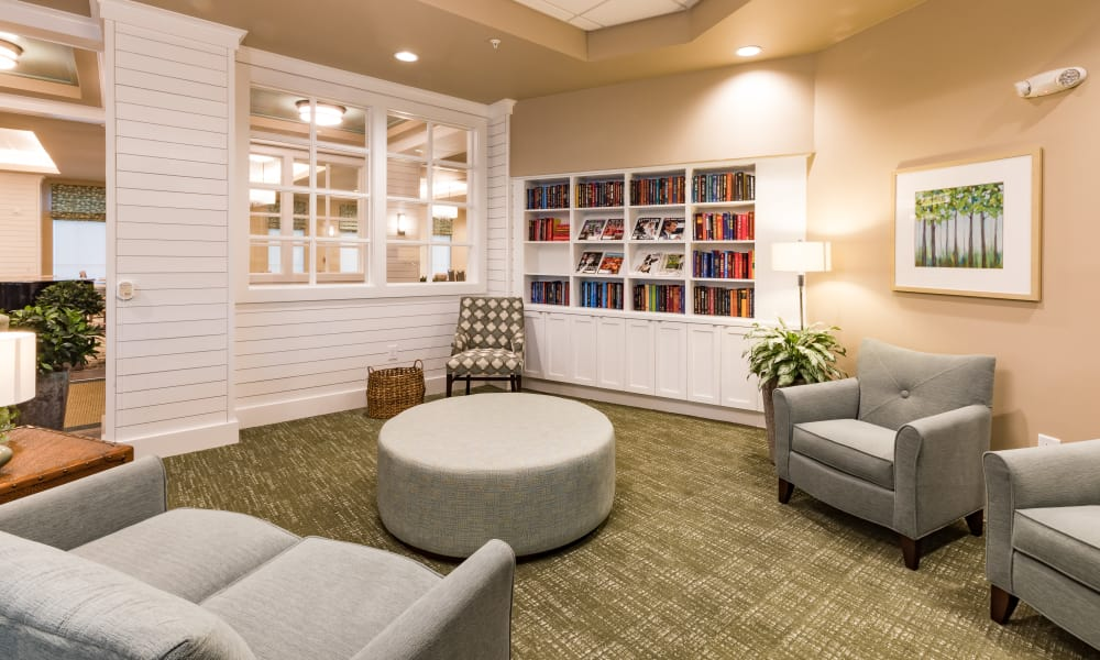 comfortable seating area with couches and books at Merrill Gardens at Carolina Park in Mount Pleasant, South Carolina.