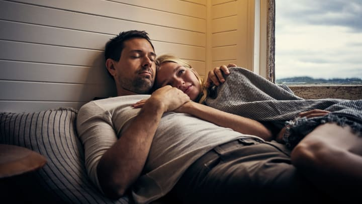 Young couple lying on a bed in a vacation home