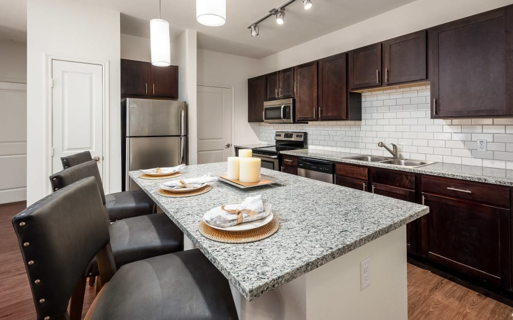Granite countertops and subway tile backsplash in model home's kitchen at 4 Corners Apartments in Frisco, Texas