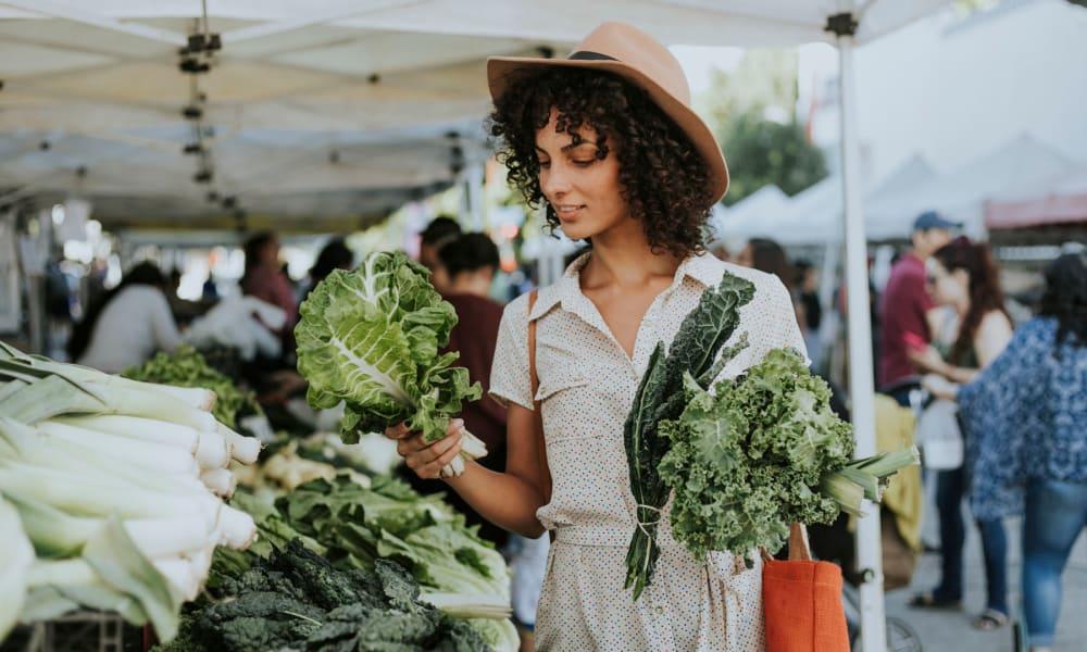 Resident shopping for fresh produce at a farmers market near Pleasanton Heights in Pleasanton, California