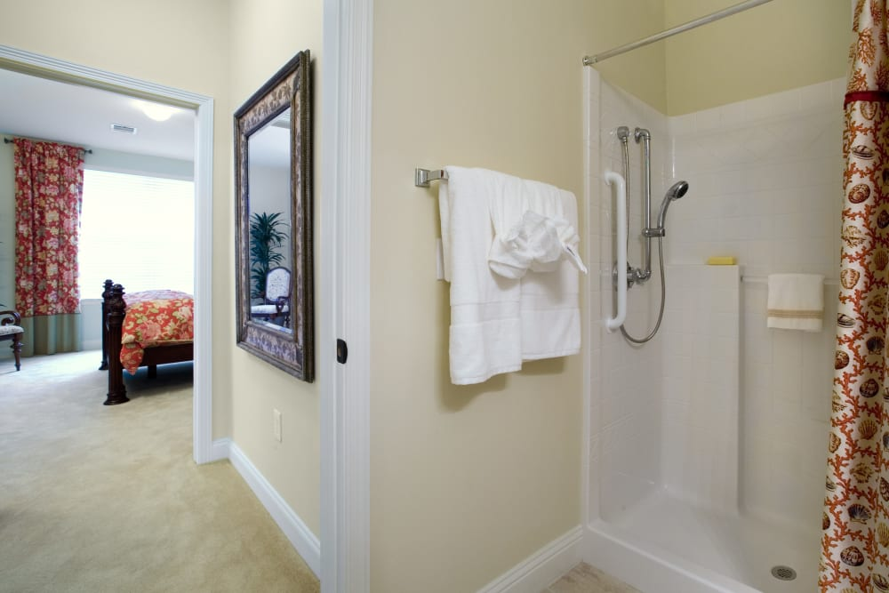 An apartment shower in the bathroom attached to a bedroom at The Village of Tanglewood in Houston, Texas