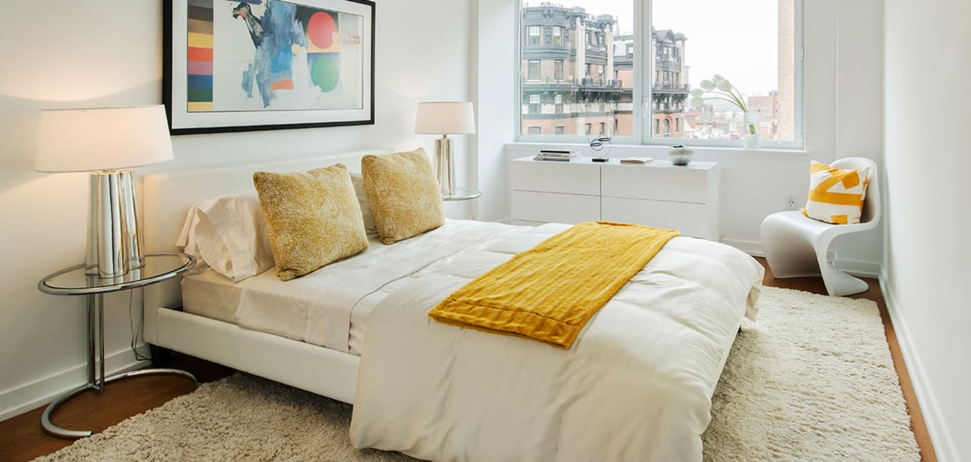 A bright and open master bedroom with a large window at The Larstrand in New York, New York