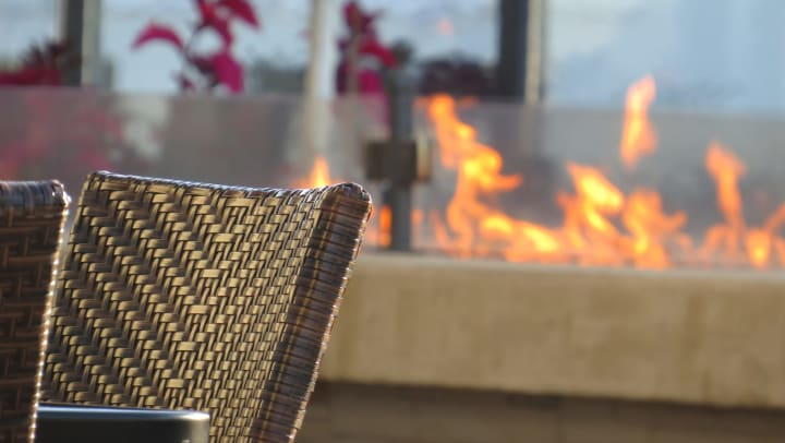 Outdoor dining area with fire pit in the background.