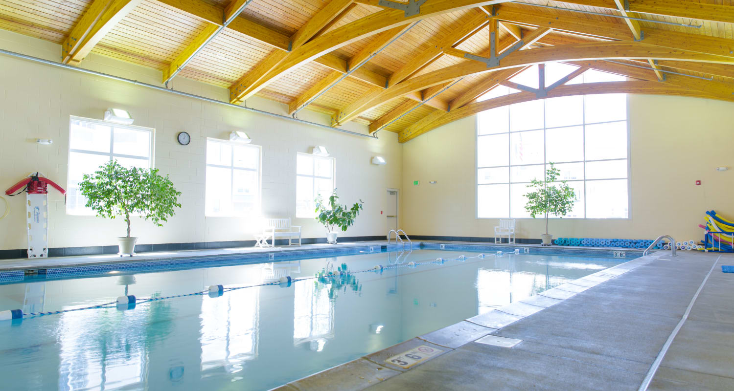 The pool surrounded by large windows at Touchmark at Harwood Groves Health & Fitness Club in Fargo, North Dakota