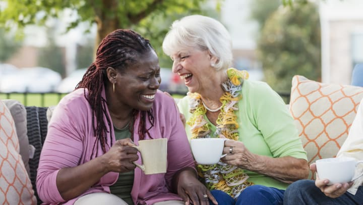 Two elderly women drinking out of coffee cups and laughing