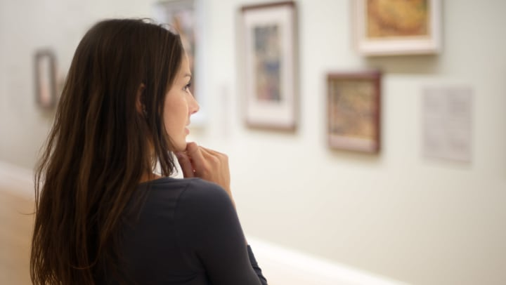 Shot of a young woman thoughtfully looking at pictures in an art gallery.