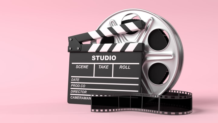 Movie film reel with a clapperboard on a pink background