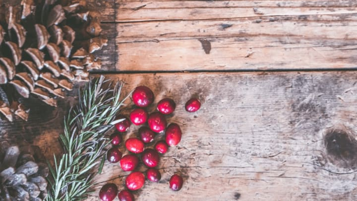Christmas pinecone, cranberries, and pine on a wood table