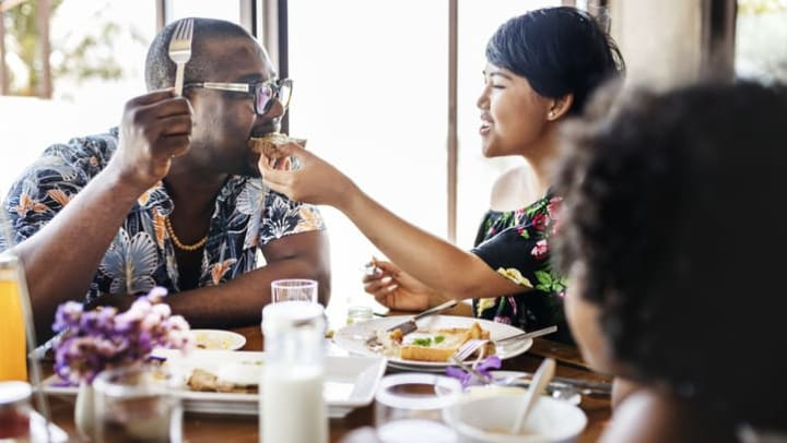 Woman feeds man a bite of her brunch at a table in a restaurant near {{location_name}} in {{location_city}}, {{location_state_name}}