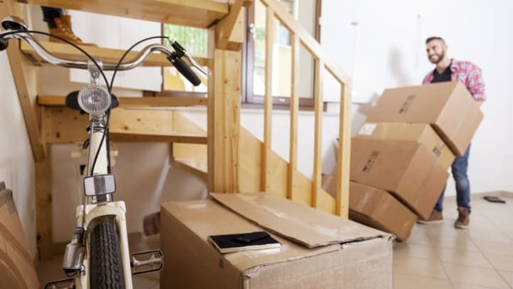 Young man moving boxes in a house, with a bicycle in the foreground near {{location_name}}.