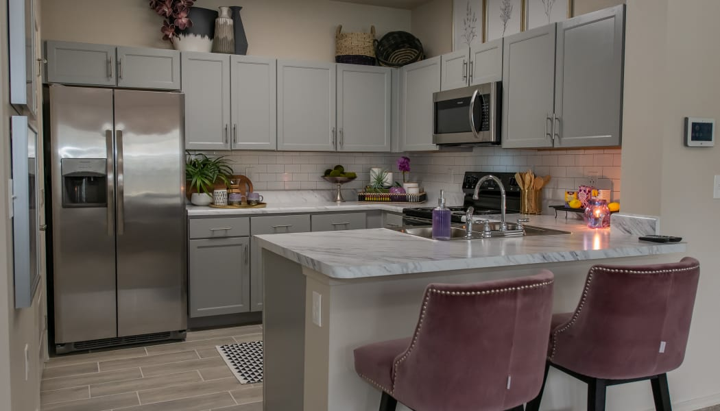 Modern kitchen with granite counters at Bend at New Road Apartments in Waco, Texas