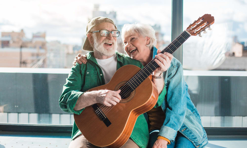 A resident from Touchmark in the West Hills in Portland, Oregon playing a guitar for another resident