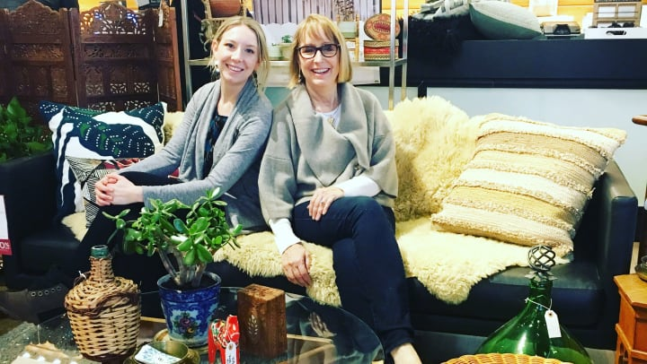 Two smiling women -- Carla and Taylor -- are sitting on a couch in front of a coffee table