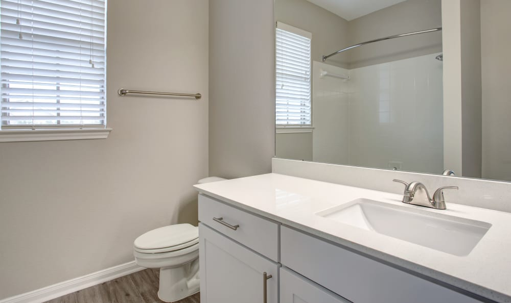 Quartz countertop and a large vanity mirror in a model home's bathroom at Riata Austin in Austin, Texas