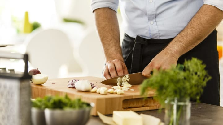 Man with only arms visible slicing garlic on a cutting board with other ingredients, with a stick of butter and herbs visible in the foreground.