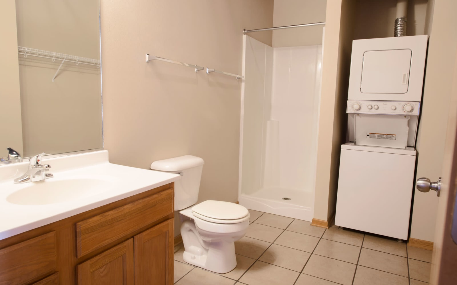 Studio apartment bathroom with a stacked washer and dryer at West Towne in Ames, Iowa