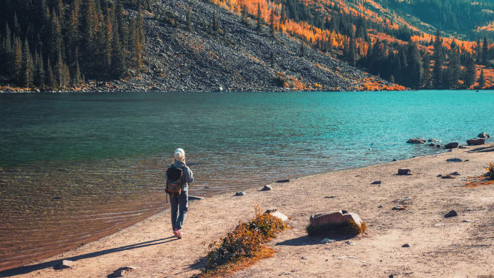 A person stands in front a body of water with mountains and fall foliage in the distance
