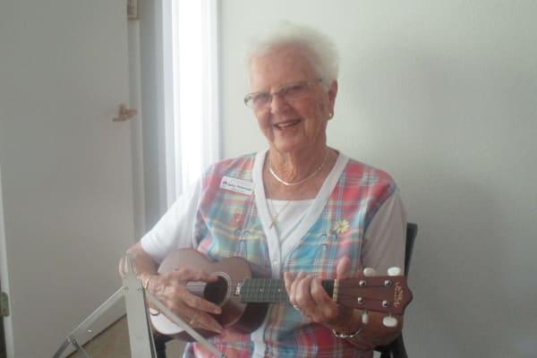 Resident Betty playing the ukulele at Discovery Senior Living in Bonita Springs, Florida