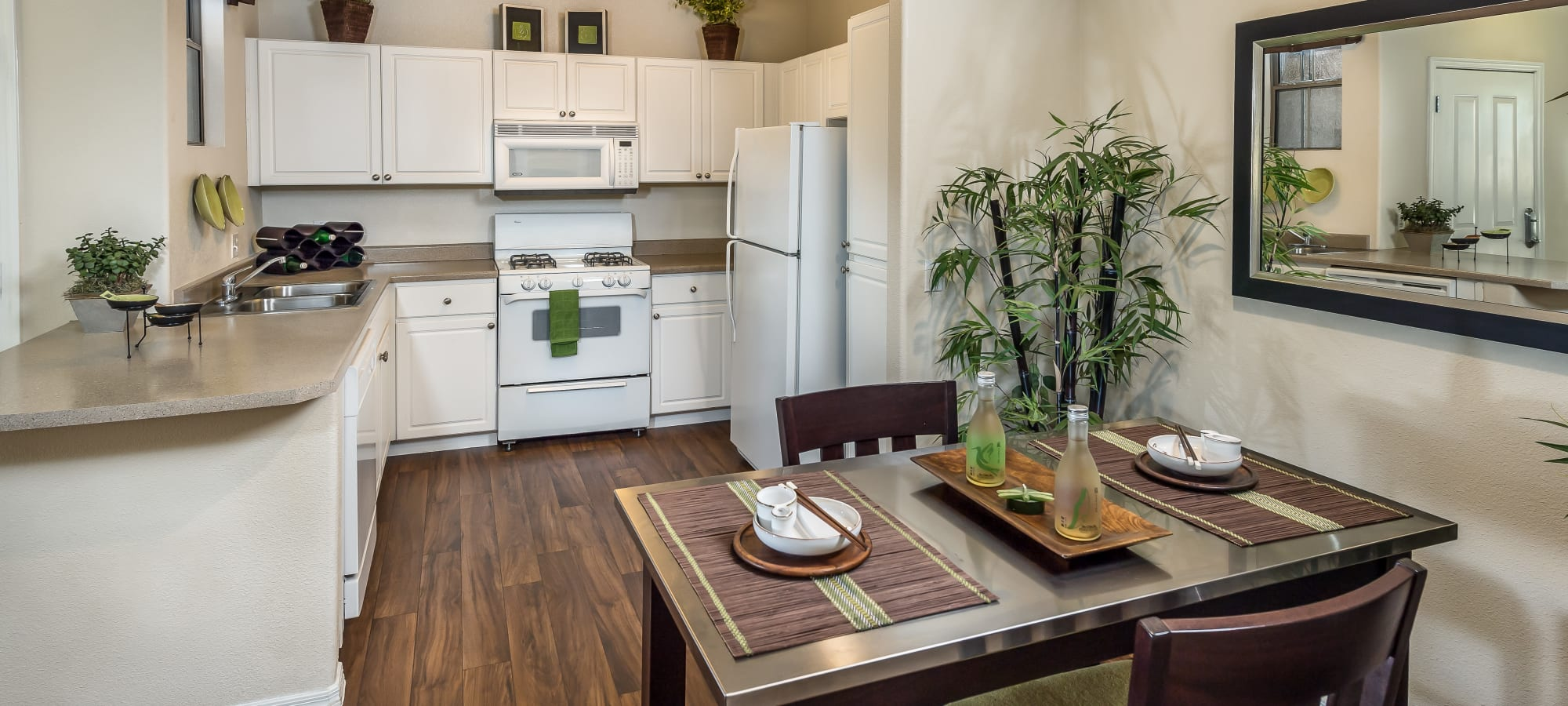 View of the modern kitchen next to the dining area of a model home at Stone Oaks in Chandler, Arizona