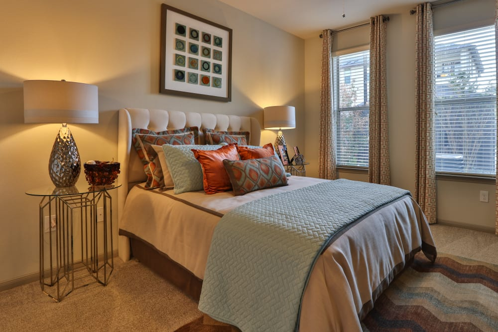 Ceiling fan and plush carpeting in a model home's bedroom at Olympus at Waterside Estates in Richmond, Texas