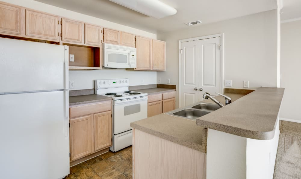White appliances in a model home's kitchen at Riata Austin in Austin, Texas