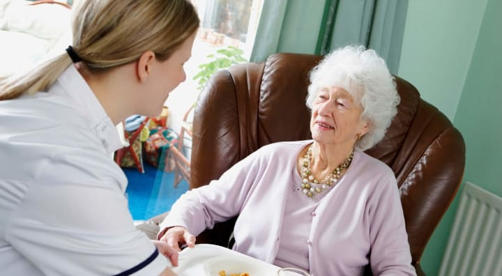 Caregiver serving senior food in apartment