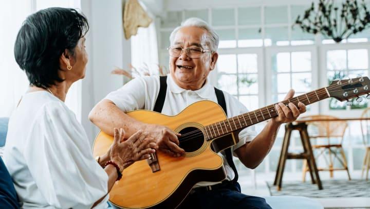 Senior man playing guitar for wife