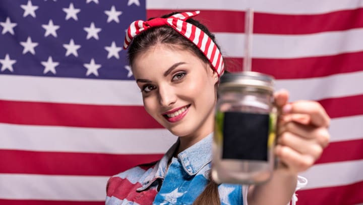Woman with a red and white striped headband standing in front of American flag holding a Mason jar beverage holder with straw toward the camera.