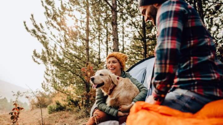 Man and woman outdoors surrounded by camping equipment, the woman is hugging a golden retriever.