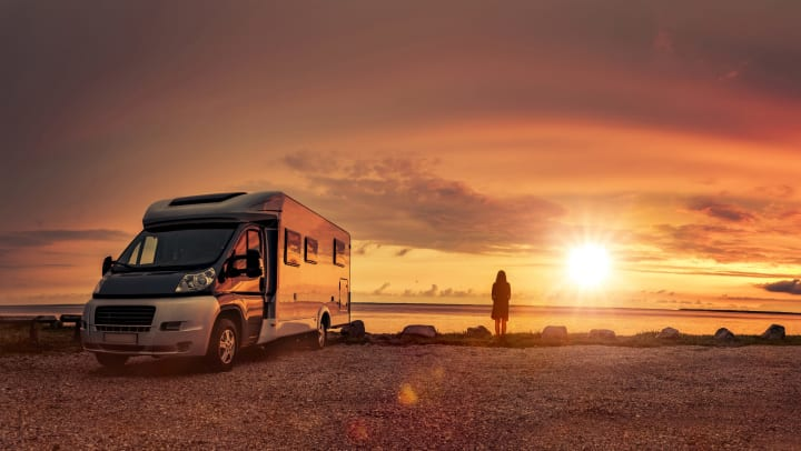 Picture of an RV and a woman looking at the sun setting over the ocean