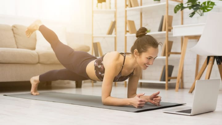 Woman doing yoga while looking at a laptop