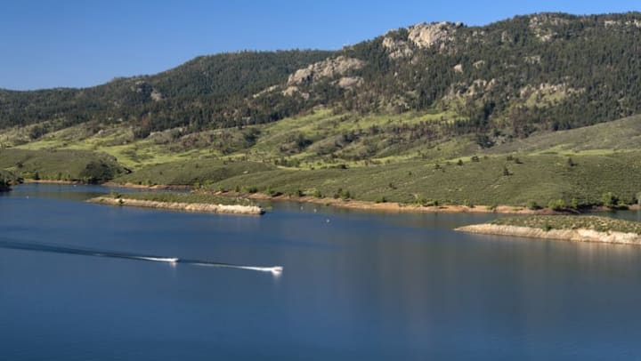 Boaters zoom across Horsetooth Reservoir near {{location name}} in Fort Collins, CO.