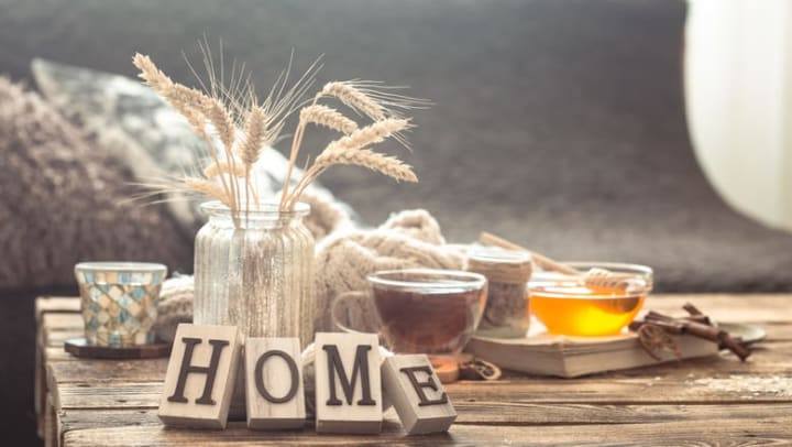 """Still life details of home interior on a wooden table with the word """"home"""" spelled out in wooden letter blocks at {{location_name}}."""