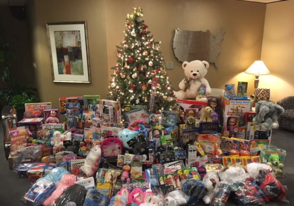 Hundreds of presents under the Christmas tree about to go to families in need from American Capital Group in Bellevue, Washington