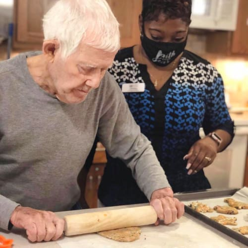 Resident cooking with help from a caretaker at Oxford Glen Memory Care at Sachse in Sachse, Texas