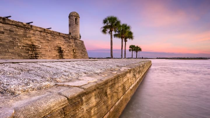 Sunset picture of palm trees, the Atlantic Ocean, and the limestone walls that make up the Castillo de San Marcos historic fort near {{location_name}}