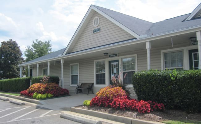 Clubhouse exterior surrounded by flower beds at Station 153 Apartment Homes in Anderson, South Carolina