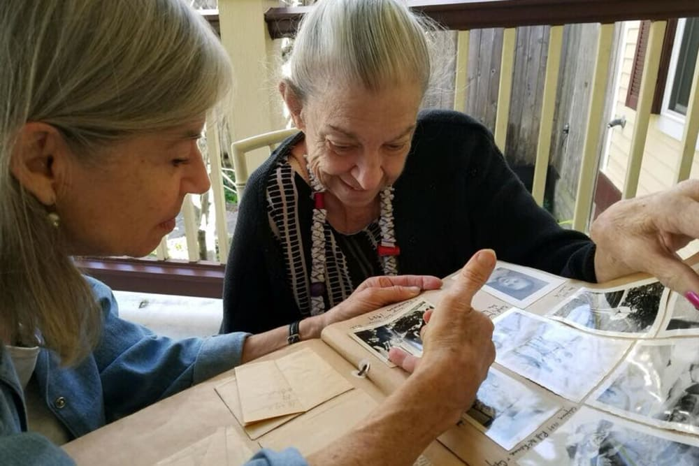 Residents looking through a photo album at Autumn Grove Cottage at The Heights in Houston, Texas