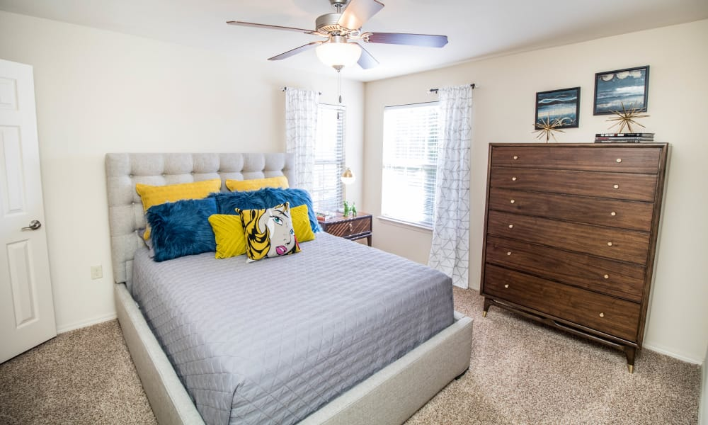 Bright bedroom with tall windows at Tuscany Place in Lubbock, Texas.