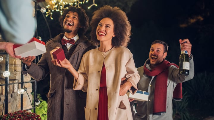 Two warmly dressed men and a woman smiling and holding gift boxes and a bottle of champagne, are on the front porch of a home decorated with holiday lights.
