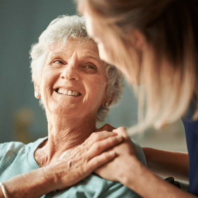 A resident and care giver hold hands at Milestone Retirement Communities
